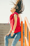 Girl on stairs in city. Young long haired girl on city stairs feeling wind in hair. Lifestyle funky in summer Royalty Free Stock Photos