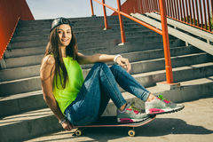 Girl on stairs with skateboard. Stock Photo
