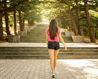 Girl on stairs in the sun stock photography