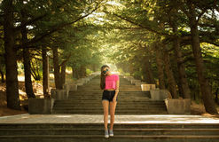 Girl on stairs in the sun stock photo