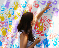 Girl stamps trace hands on wall with prints Royalty Free Stock Image