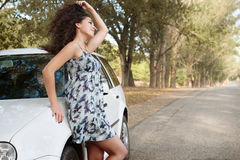 Girl stand on country road near auto, big high trees, summer season Stock Photo