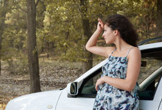 Girl stand on country road near auto look into the distance, big high trees, summer season Stock Image