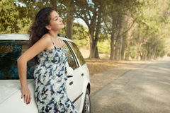Girl stand on country road near car, big high trees, summer season Stock Image
