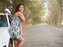 Girl stand on country road near car, big high trees, summer season Stock Images