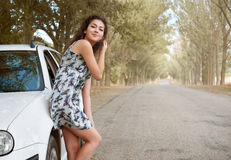 Girl stand on country road near car, big high trees, summer season Stock Photo
