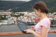 Girl stand on deck of ship with laptop Stock Images