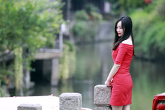 A girl stand by a lake in Feng Jing ancient town. In Feng Jing ancient town, a girl with red dress stand by a lake.smiling, smile. look at the lake, there are Stock Photo