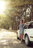 Girl stand near car on country road, bright sun and trees, summer season Royalty Free Stock Photography