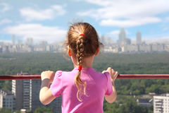 Girl stand of roof of high building. Little girl stand of roof of high building look on city, back Stock Photography