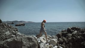 Girl stand on rough stones of sea shore and look at high rise building construction on other harbor side stock video