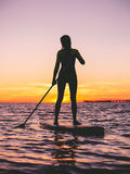 Girl stand up paddle boarding at dusk on a flat warm quiet sea with sunset colors. Girl relaxing on stand up paddle board, on a quiet sea with sunset colors Royalty Free Stock Photo