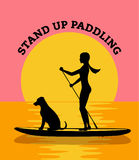 Girl Stand up Paddling with her dog at sunset Stock Photos