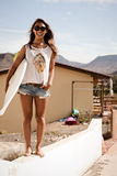 Girl stand on wall with a surfboard. summerfeeling Stock Images