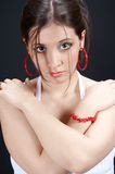 Girl standing. Girl with red earings on black background royalty free stock photography