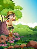 A girl standing above the rock near the giant tree Stock Images