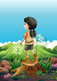 A girl standing above a stump Stock Photo