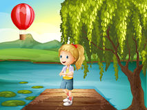 A girl standing above the wooden bridge with a hot air balloon n Royalty Free Stock Photo