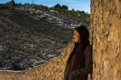 Girl standing against a stone wall in an old town with mountains Stock Images