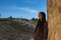 Girl standing against a stone wall in an old town with mountains Royalty Free Stock Photos
