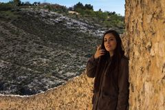 Girl standing against a stone wall in an old town with mountains Stock Photos