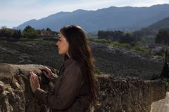Girl standing against a stone wall in an old town with mountains Stock Image