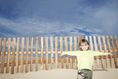 Girl Standing Against Wooden Fence On Beach Royalty Free Stock Photos