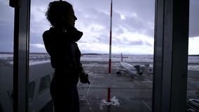 Girl standing at the airport near a large window looking out on the planes that are on the runway. Silhouette of a young stock video
