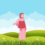 Girl standing alone in green field land wearing veil scarf Royalty Free Stock Photo