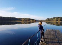 A girl is standing alone on a wooden pier by the lake. A girl in a blue jacket is standing alone on a wooden pier by the lake on an autumn day Stock Photos