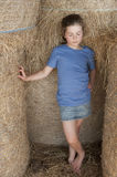 Girl standing amongst bales of hay Royalty Free Stock Images