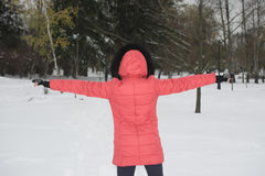 Girl standing, arms to the side, in the winter. With his back to Stock Image
