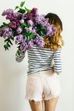 Girl standing back with a bouquet of lilac on a white background stock photography