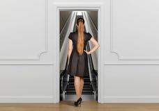 Girl standing back to doorway going on escalator Stock Image