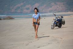 The girl is standing on the background of a motorcycle on the be. Ach, dressed in sexy shorts Royalty Free Stock Image