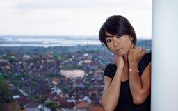 Girl standing on the balcony. dressed in black short dress. Stock Photo