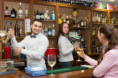 Girl standing at bar with glass of wine. Happy smiling girl standing at bar with glass of wine and flirting with barman. Focus on guy Royalty Free Stock Photos
