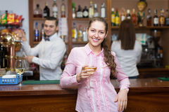 Girl standing at bar with glass of wine Stock Photography