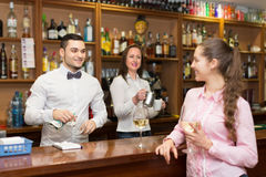 Girl standing at bar with glass of wine. Young attractive girl standing at bar with glass of wine and flirting with barman. Focus on guy Stock Photo