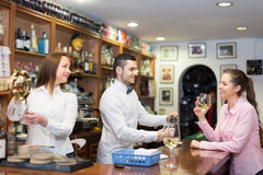 Girl standing at bar with glass of wine. Young smiling girl standing at bar and holding glass of wine. Focus on guy Stock Photos