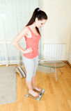 Girl standing on bathroom scales royalty free stock photography