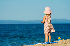 Girl standing on beach. Girl in dress and hat standing on the beach and looks into the distance royalty free stock photography