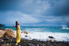 Girl standing on the beach against the sky and the sea Stock Images