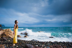 Girl standing on the beach against the sky and the sea Royalty Free Stock Image