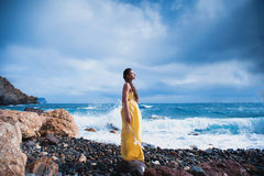 Girl standing on the beach against the sky and the sea Stock Photography