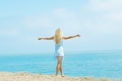Girl standing on the beach arms outstretched Stock Image