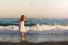 Girl standing at the beach Stock Photos