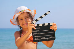 Girl standing on beach and holding clapboard Royalty Free Stock Photo