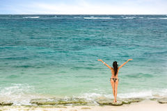 Girl standing on the beach and looking at sea Stock Images