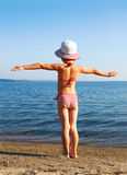 Girl standing on the beach in a striped bathing suit Royalty Free Stock Photos